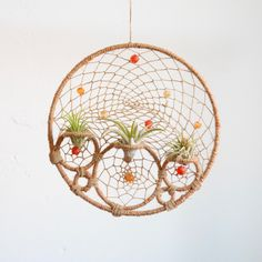 Natural jute and hemp cording are intertwined through out this multi-ringed dream catcher. Brilliant orange and red recycled glass beads handmade in Ghana, Africa are sprinkled amongst the six earthy rings. This dreamcatcher features three air plants tucked into three jute covered rings. PLANT CAR
