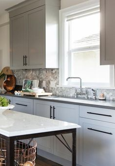 Love It or List It - Fantastic kitchen features gray shaker cabinets adorned with oil rubbed bronze pulls paired with charcoal grey quartz countertops and a white and gray hex tiled backsplash.
