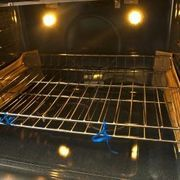How to Clean Oven Racks Naturally  -- The appliance repairman advises that 'using the self-cleaning feature takes years off the life of an oven.' Better to:   Cover bottom of oven with baking soda, then pour vinegar so it's all wet. Let sit around 20 minutes, then wipe all of it out with damp cloth or sponge. After drying there maybe some white residue, wipe again.