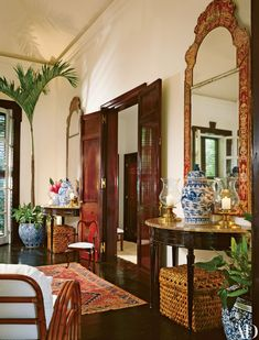 Asian accents, such as antique ginger jars and chinoiserie mirrors, contribute to the living room's exotic feel.