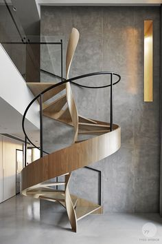 This intriguing timber staircase set before a moody expanse of concrete has immense visual appeal with its beautiful almost helix-like central twist and it's smooth sweeping exterior. By YYDG InteriorDesign.