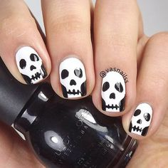 Scary skeleton faces nail art for Halloween. Make your nails extra spooky with these Halloween skeleton faces painted in white polish against a black base coat.