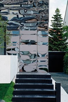 German architect Bernd Zimmermann has recently renovated a three-family house from the 50′s near Stuttgart for a married couple, coating the exterior of the house with hundreds of funhouse mirrors.