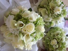 Ivory roses, ivory lilies and green hydrangea posy style bouquet.
