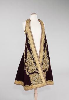 The careful placement and execution of motifs on this sleeveless coat are an example of fine workmanship. The use of solid color insets within the gold couched forms adds a gem-like quality to an extravagant surface.