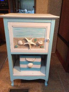 Nautical facelift to an old jam cupboard by gluing sand and shells onto door.