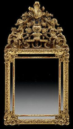 A Louis XV giltwood mirror mid 18th century The pierced arched cresting centered by a flower filled basket enclosed by C-scrolls and foliate boughs terminating in flower heads surmounted by an acanthus plume over a rectangular mirror plate enclosed by foliate panels and rectangular slips divided by acanthus and foliate brackets. height 53in