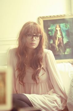Long wavy brown hair with straight across bangs and big glasses
