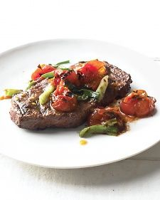 In just 20 minutes, prepare affordable, flavorful flat-iron steaks with a grilled topping of sweet tomatoes and savory scallions.