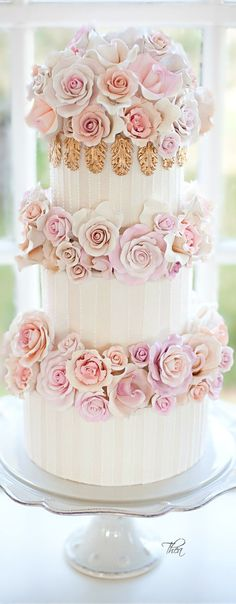 Three Tier White and pink wedding cake with pink roses.