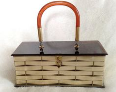 This listing is for a vintage box purse by Dorset Rex Fifth Avenue. This unique handbag has a two-tone chrome and gold basket weave exterior. The hinged top is fashioned from opaque white swirled Lucite. The handle is in coordinating clear Lucite. The purse closes securely with a latch and hook on the front.  The clean interior is lined in cherry red grosgrain fabric. It has a pleated pocket inside. The bottom of this purse has an open weave allowing the red interior to show through the…