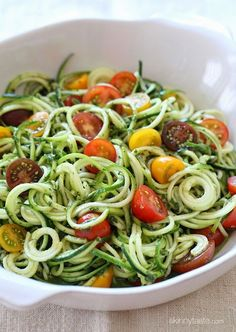 Raw Zucchini Noodles w/Tomatoes & Pesto - Makes 9 servings -Per serving 1 veg, 1 fat, 1 condiment-  Pesto: 1 cup packed fresh basil 1 clove garlic 1/4 cup fresh grated parm cheese ¼ teaspoon salt   ¼ teaspoon pepper 3 tbsp extra virgin olive oil For Zoodles: 23 oz (3 med or 4 small) zucchinis -1 cup heirloom grape or cherry tomatoes, halved -¼ teaspoon salt -½ tsp  pepper