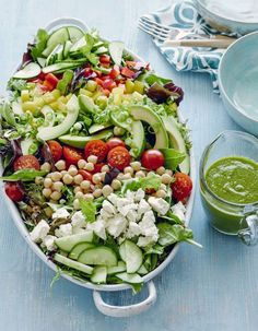A healthy loaded power salad made with cucumbers, bell peppers, avocado, green onions, tomatoes, chickpeas and feta and served with a basil vinaigrette.