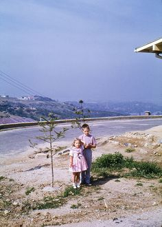 My sister Karen Smothers and me in October, 1959, next to our home in New Itaewon, on the lower southeastern slope of Namsan Mountain, south of Seoul, Korea. The photographer is facing south. In the background to the right is Yongsan, where the US 8th Army Compound is located. The ground where my sister and I are standing is now part of Namsan Park & to our left off-picture is the site of the modern day Grand Hyatt Hotel. Leroy Smothers.