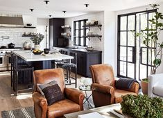 """""""Over the years I took on the role of family cook, so one of Katherine's early visions for the kitchen was to make it feel like a masculine space that I had ownership over,"""" says Coit of the black-and-white space. Leather bar stools by Thomas Hayes and antique armchairs in the adjoining den add organic warmth to the slick marble countertops, stainless appliances, and ebonized cabinetry."""