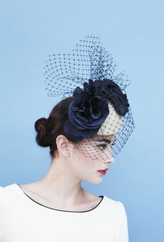 Millenium Event Hat, £375.00   Sculptural Pill Box Hat with Bird Cage Veiling. The most beautiful, quirky but adoringly chic pill box style hat, named Millenium.  The wonderful sculpted piece has been hand blocked and crafted and designed by British Designer Gina Foster.  Sculpted from oyster sinnamay with navy corsage and bird cage veiling detail.The wonderful piece has the perfect height and charm. This perfect piece of luxury millinery will compliment any neutral or chic colour pop dress.