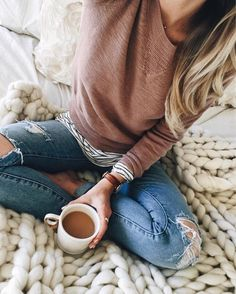 Striped long sleeve shirt layered under a mauve sweater with distressed jeans. Cute fall outfit