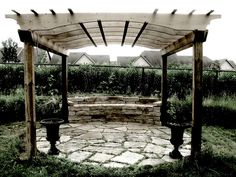 Beautiful, simple pergola over round stone patio with built-in seating.