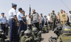 Indonesian President Susilo Bambang Yudhoyono, center, holds an assault rifle as he inspects the task force that will be deployed to help battling forest fires on Sumatra island, at Halim Perdanakusumah AFB, Jakarta.