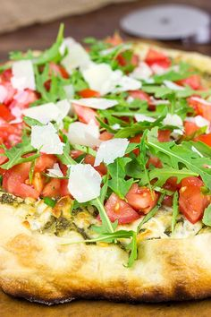 Brushed with pesto and then topped with fresh tomatoes and arugula,  this Bruschetta Pizza is a delicious summer meal!