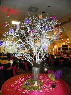 Centro de mesa para una fiesta de Quinceañera hecho ramas de arboles y decorado con mariposas de colores. #DecoracionQuinceañera #CentroDeMesa