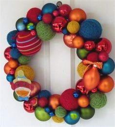 exterior want.  gorgeous wreath!  i love the mix of shiney ornaments with yarn balls.  i would likely only put a ball wreath out around christmas, so lime greens, bright reds, with aqua/white accents