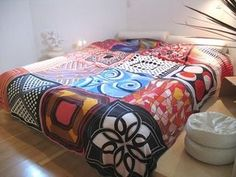 This bedcover is made of square silk scarves simply sewn together.
