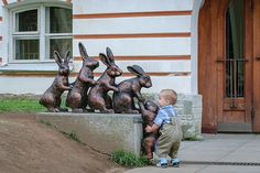 Child stops to help bunny statue