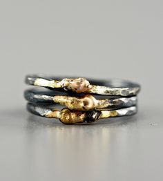 Fabricated in an organic, primitive shape, these metal rings are each a one-of-a-kind pairing of oxidized silver and touches of gold.