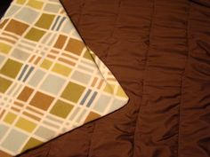 """Here's the weighted blanket I'm in the process of making for my Hubby for his B-day.  Satiny chocolate fabric on the """"cool"""" side and a earthtone fleece fabric on the """"warm"""" side.  Filling the chambers with poly pellets and it will be complete."""