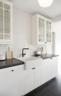 Black and white kitchen features glass front upper cabinets and white beadboard lower cabinets adorned with oil rubbed bronze hardware paired with  black countertops fitted with a farmhouse sink and modern bronze faucet as well as a white beveled subway tile backsplash.