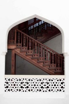 Sterling white wall with a large arch way opening. Dark wood ornamented stair steps and lace lattice work along the arch way opening.