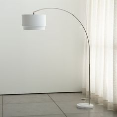 Shop Meryl Arc Floor Lamp. The arc floor lamp goes over and above modern expectations, suspending a geometric two-tier shade in crisp white cotton blend from a satin nickel-finished arch. Round white marble base adds a classic touch.