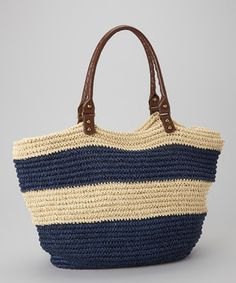 Inspired by seaside style, this two-tone tote is made from woven paper straw. The classic stripe design enhances its nautical charm.