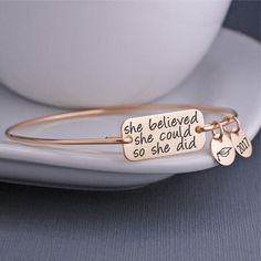 """A 14k gold filled, 14k rose gold filled or stainless steel rectangle measuring 1 1/8 of an inch across is engravedwith the words """"she believed she could so she did"""".The bracelet band is 14k gold filled, 14k rose gold filled, or sterling silver.Each bangle is hand formed, then hammered and tumbled for shine and strength. Bangles do not have clasps and they slide over the hand. CHARMS ARE OPTIONAL.Need help determining size? Click here."""