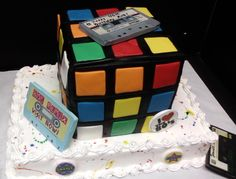Rubik's Cube made from fondant. Cassette tapes and buttons are edible images mounted on fondant. Splatters are food color gels mixed with a little Vodka and splattered with small paint brush.