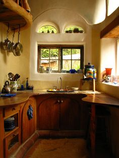 (via My Intro to Cob « Natural Living School) the kitchen of laughing house at cob cottage… but then with the cupboard doors in whitewash.