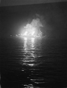 "The light cruiser HMS Belfast pounding German positions at night around Normandy. She is using her secondary 4"" guns rather than her main 6"" guns."