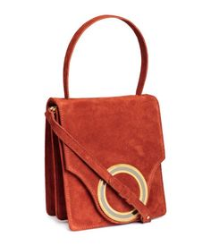 PREMIUM QUALITY. Handbag in suede with a handle, detachable adjustable shoulder strap, and flap with metal decoration and magnetic closure. Inner compartment divided by center compartment with zip. One inner pocket. Lined. Size 4 1/4 x 7 1/2 x 8 1/4 in.