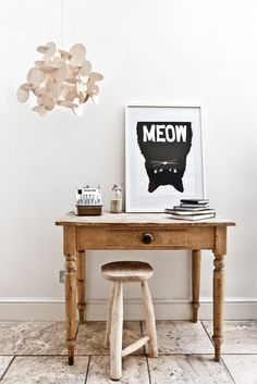 """Small wooden desk and stool with framed """"Meow"""" cat print, wooden mobile, and antique objects."""