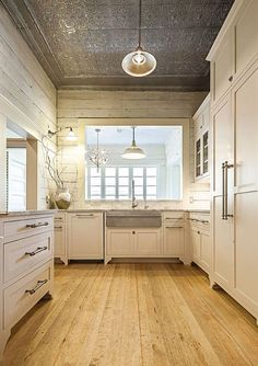 Long plank wood floor, tin ceiling, white kitchen, farmer's sink, rustic kitchen