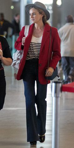 Kruger was the picture of polished French-girl perfection in a bright red coat over a striped shirt casually tucked into her flared jeans at Charles-Gaulle airport in Paris.
