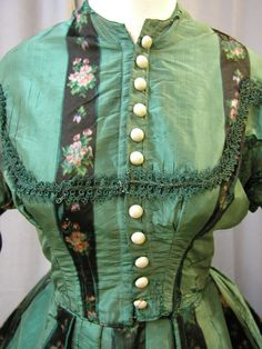 1860's Emerald Green silk & Floral Stripe Dress: What a beautiful fabric. This 1860's dress is made of stripe silk taffeta. The wide green stripes were originally striped with a fine black stripe. The photo of the back shows this detail. For some reason most of the black thin stripes have faded out. The sleeves are Juliet type treatment. The buttons are ivory silk faille. The bust is 38, the waist is 30, the skirt length in front is 42 and it is 47.5 in back. It is 132 inches around the…