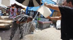 A man pours water on another man in Baghdad on 30 July, 2015
