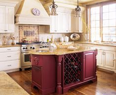Designed as a focal point, this oxblood-red kitchen island optimizes the kitchen's storage capacity by housing built-in wine storage and refrigerator drawers. Combined with the presence of a bar sink, the storage features make the island perfect for serving drinks and appetizers.