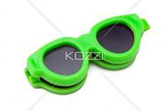 green retro sunglasses against white background. - Close-up image of a green retro sunglasses against white background.