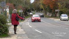 Auto stoppeuse. Femme faisant de l'auto stop sur une route de campagne, vue de dos avec un manteau rouge et une jupe noire.