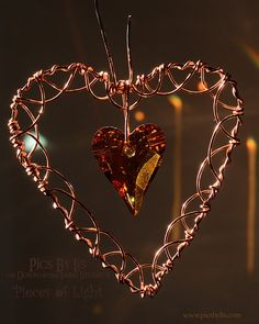 "This copper heart suncatcher is made of copper wire with a large copper Swarovski® Heart Crystal in the center of the heart. Measures approximately 3"" in height and 2 5/8"" in width. Would make a stunn"
