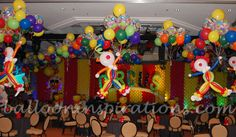 ... the room , including the fun filled table decorations consisting of a floating balloon clown sculpture holding a large bunch of multicoloured balloons.