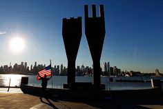 Jeremy Hamilton places a United States flag next to a memorial bearing two pieces of steel from the World Trade Center in Weehawken, N.J. across from the skyline of New York. Thousands will gather in New York, Washington and Pennsylvania to mark the 11th anniversary of the Sept. 11 attacks. (Gary Hershorn/Reuters)